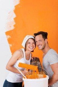 Фото счастливой пары занимающейся покраской стен в комнате