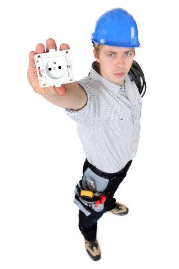 Электрик с розеткой в руках